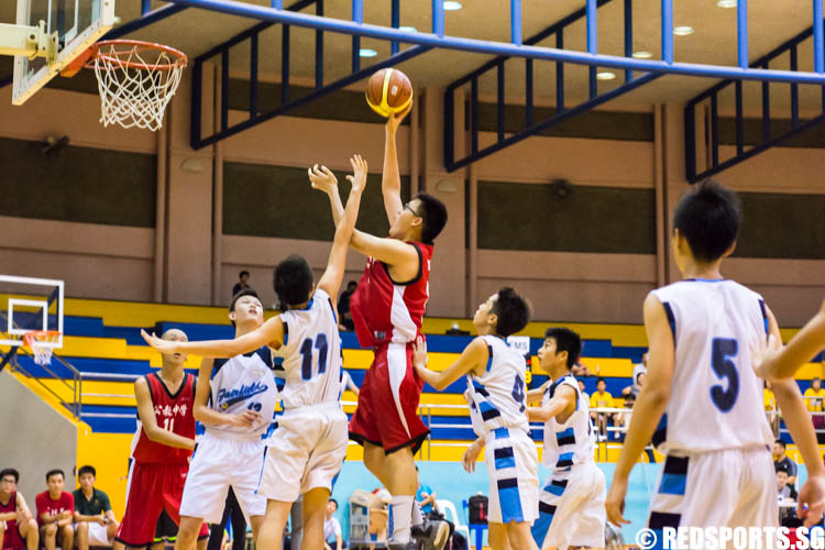 Keith Png (CHS #15) hits a hook shot over Nicholas Leong (FMS #11). (Photo 1 © Zachary Foo/Red Sports)