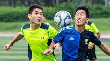 Benjamin Ong (left, #22) of Victoria Junior College and Kang Seong Soo (#19) of Anglo-Chinese Junior College challenge for the ball during their second round match of the National 'A' Division Football Championship at Victoria Junior College on May 15, 2015.