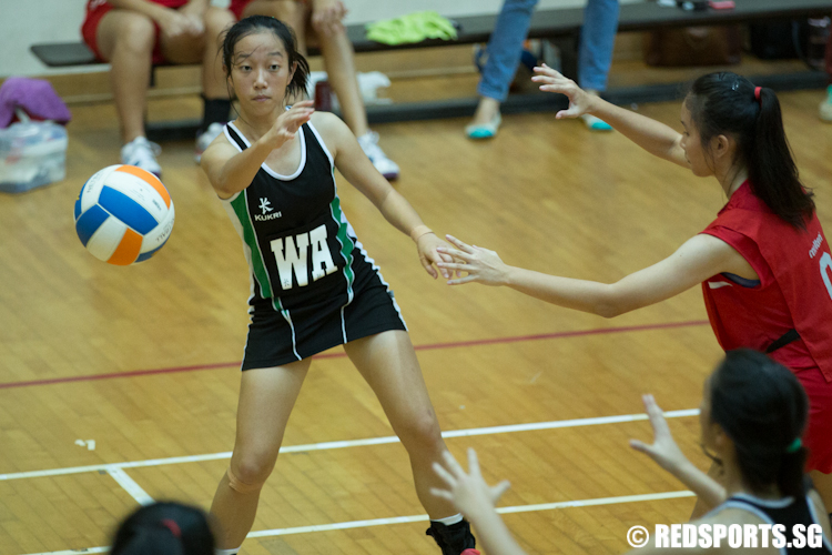 Freda Mah (WA) of Raffles Institution looks to pass the ball to Tessa (GA). (Photo © Lee Jian Wei/Red Sports)
