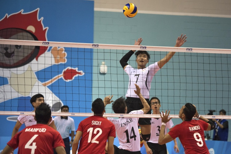 Benjamin Choo Wei Jie (#7) is set up for a spike as he rises above the net for an overhead attacking shot.