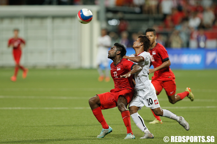 Pravin Gunasegaran (#12) of Singapore controls the ball against Thura Shine (#20) of Myanmar. (Photo © Lee Jian Wei/Red Sports)