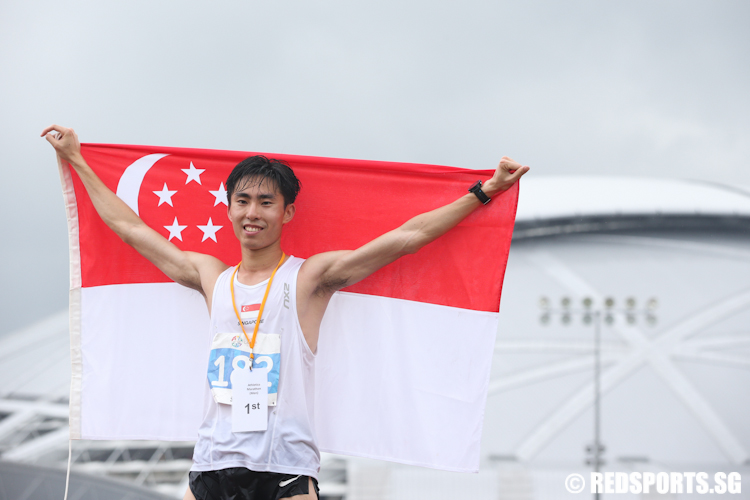 Soh Rui Yong (SIN) pose with the national flag after clinching gold with a time of 2 hours 34 minutes and 56 seconds. (Photo © Lee Jian Wei/Red Sports)