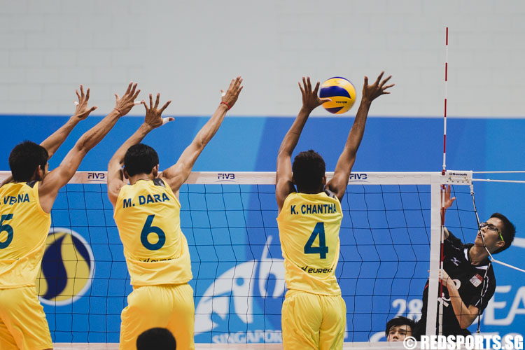 Javier Poon (SIN #3) spikes the ball while 3 Cambodian players are attempting a block. (Photo 1 © Soh Jun Wei/Red Sports)