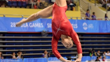 Ashley Lau executing a cartwheel as part of her dismount. (Photo 4 © Laura Lee/Red Sports)