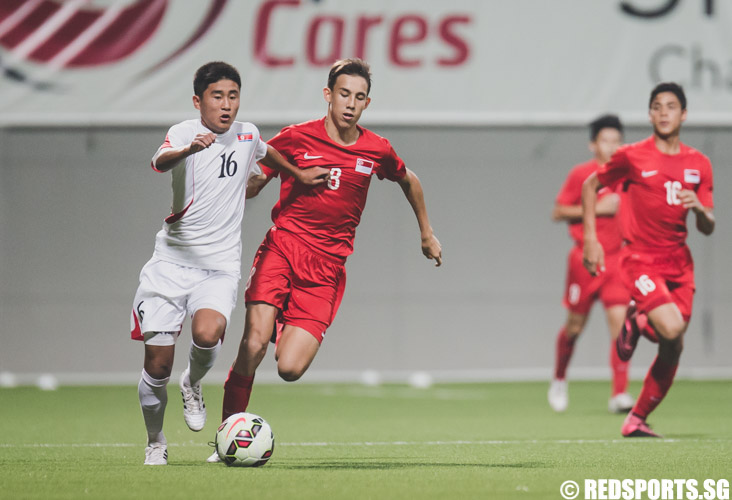 Kwon Nam Hyok (DPRK #16) dribbling the ball down the field while Mahler Jacob William (SIN #8) defends him. (Photo 4 © Soh Jun Wei/Red Sports)