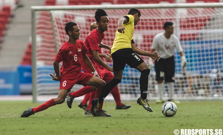 Suhaimi Bin Sudar (SIN #7) and Muhammad Taufiq Bin Baharin (SIN #6) trying to intercept the ball from Noor Mohd Ariff Bin Yusoff (MAS #7) (Photo 2 © Soh Jun Wei/Red Sports)