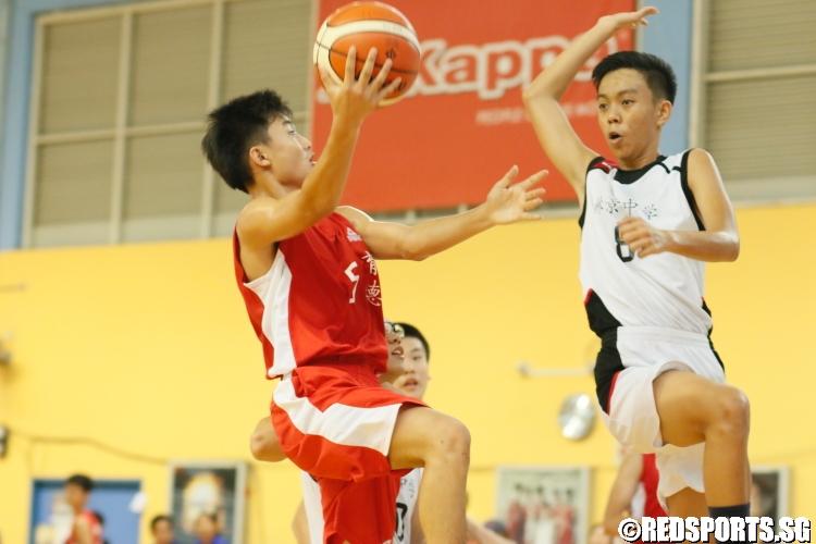 Sean Por (Edgefield #5) challenged by Seah Jin Yong (Woodgrove #8) as he rises for a layup. (Photo  © Chan Hua Zheng/Red Sports)
