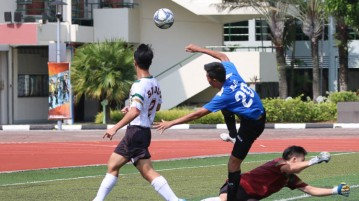 "Eldon Foo (ACJC #20) drives pass SRJC""s goalkeeper and fires a goal. (Photo © Chua Kai Yun/Red Sports)"