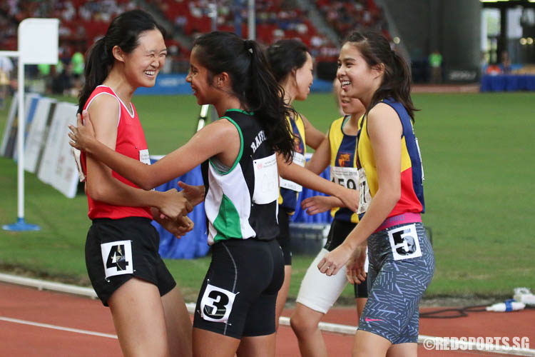 Teo Sze-Anne (left) and Amirah Aljunied (centre) sharing a moment after the A-Girls 100m sprint. (Photo © Chua Kai Yun/Red Sports)