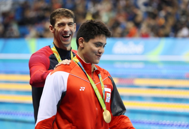 2016 Rio Olympics - Swimming - Victory Ceremony - Men's 100m Butterfly Victory Ceremony - Olympic Aquatics Stadium - Rio de Janeiro, Brazil - 12/08/2016. Joseph Schooling (SIN) of Singapore is congratulated by Michael Phelps (USA) of USA as they leave the podium.   TSRIO2016 REUTERS/Stefan Wermuth FOR EDITORIAL USE ONLY. NOT FOR SALE FOR MARKETING OR ADVERTISING CAMPAIGNS.