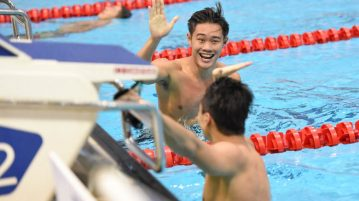 Teong Tzen Wei high fiving Dylan Koo after clocking in 24.60 at the men's 50m butterfly final to clinch third on the first day of the 13th Singapore National Swimming Championship. (Photo © Stefanus Ian/Red Sports)
