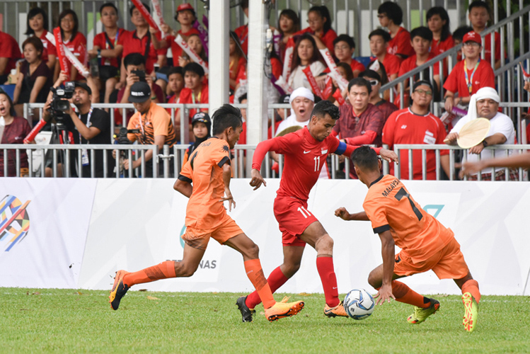 Muhammad Mubarak dribbling the ball as two Malaysian defenders close in. (Photo 1 ;copy& Stefanus Ian/Team Singapore)