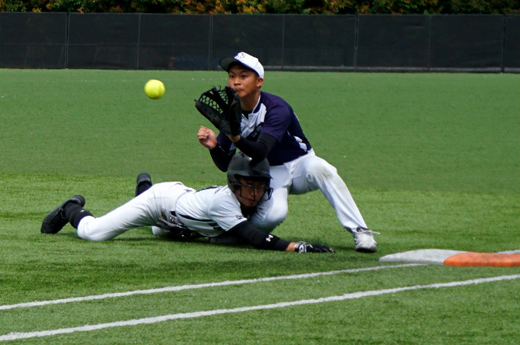 J Lim (ACSI #22) straddles the base and catches the ball from the catcher, while Max (RI #11) dives back to first base. (Photo 1 © REDintern Pang Chin Yee.)