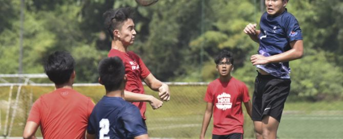 A Raffles Institution player (in red) making a free header during a NYSI JC League match between Raffles Institution and River Valley High School. (Photo © Stefanus Ian/Red Sports)