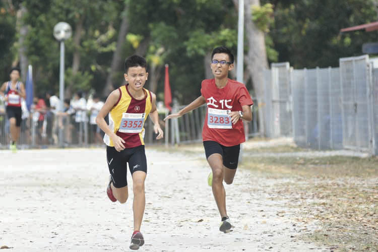 Lee Kang Zheng Russell (#3352, on the left) of Victoria School came in thirteenth with a timing of 17:41 in the B Division Boys. (Photo © Eileen Chew/Red Sports)