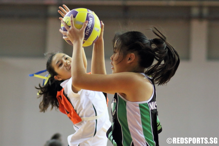 Michelle Ong (GS) of RGS catches a pass over the outstretched arms of her defender. (Photo  © Chan Hua Zheng/Red Sports)