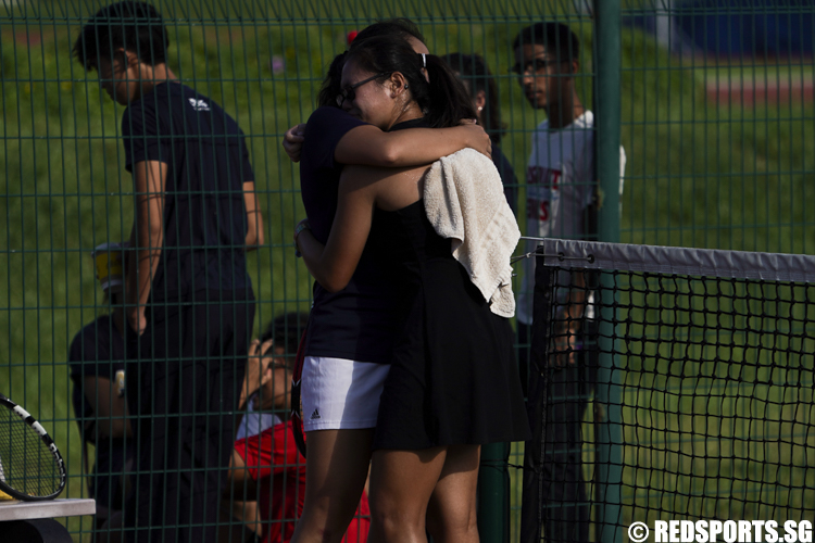 Tamara Tan of Raffles Institution and Elizabeth Lee of Anglo-Chinese Junior College shares a moment after their singles match. (Photo © Lee Jian Wei/Red Sports)