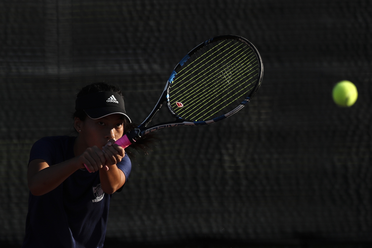 Nadine Loh of Anglo-Chinese Junior College plays a backhand against Tammy Tan of Raffles Institution during her singles match.
