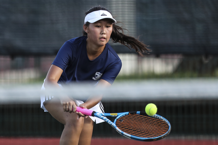 Natalie Tan of Anglo-Chinese Junior College plays a backhand against Jeovanne Poernomo of Raffles Institution during her singles match.