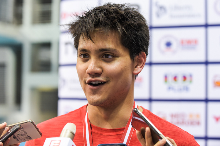 Joseph Schooling speaking to the media after winning the 100m butterfly finals with a new meet record of 52.43s at the 14th Singapore National Swimming Championship. (Photo 2 © Eileen Chew/Red Sports)