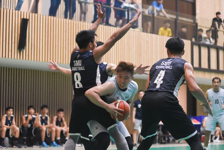 Ng Kian Hao (SIM #27) grabbing an offensive rebound while being surrounded by SMU players during the match. (Photo 1 © Stefanus Ian/Red Sports)