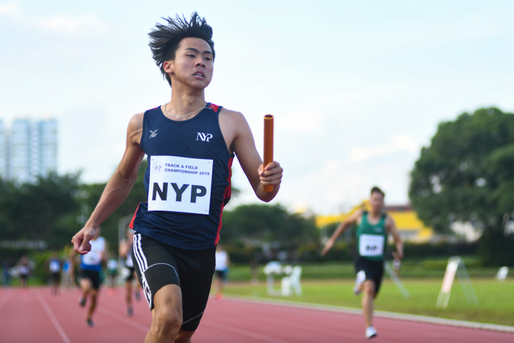 Joshua Chua of Nanyang Polytechnic crossing the finish line second in the 4x100m Men's Relay, but a botched baton handover in the first exchange zone meant his team got disqualified. (Photo 1 © Stefanus Ian/Red Sports)