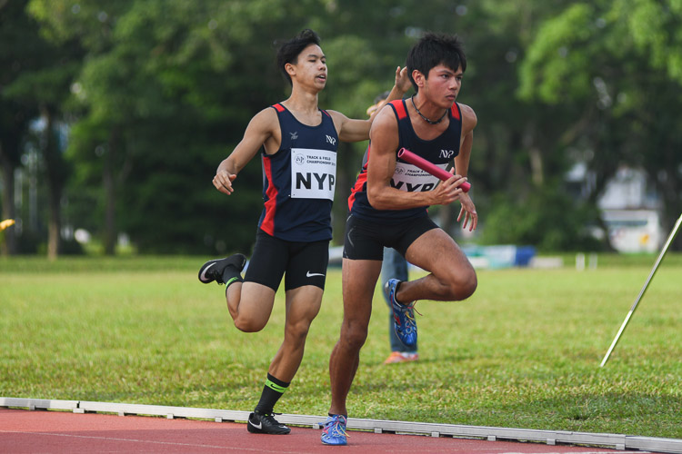 Ian Matthew Ngui of NYP passes the baton over to teammate Russell Hari Chandra in the second men's 4x400m relay timed final. (Photo 25 © Stefanus Ian/Red Sports)