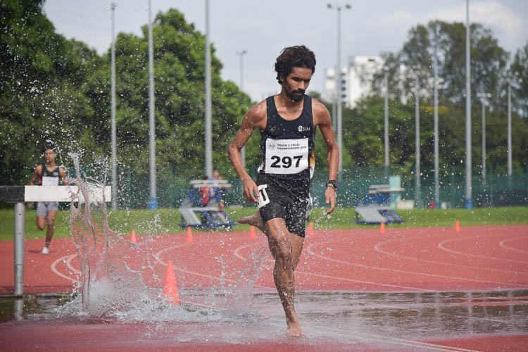 Nabin Parajuli of SIM (#297) going through the water jump during the Men's 3000m Steeplechase race. He clinched gold with a time of 9:44.04. (Photo 1 © Iman Hashim/Red Sports)