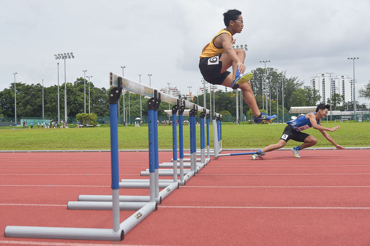 Ervin Teo (in blue) stumbling during the Men's 400m Hurdles race as Lukas Tan (in yellow) jumps over the hurdle. They finished with a time of 1:16.18 and 1:11.51 respectively. (Photo 1 © Iman Hashim/Red Sports)