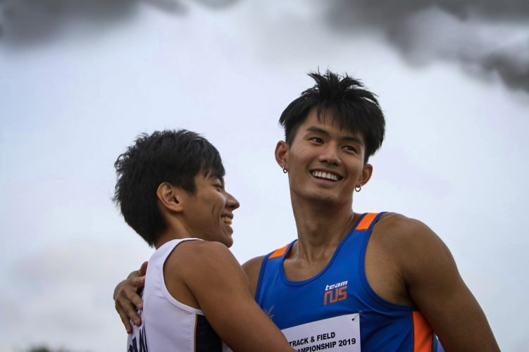 Timothee Yap of NUS and Tan Zong Yang of SMU hug after a close fought race between 1st and 2nd place.