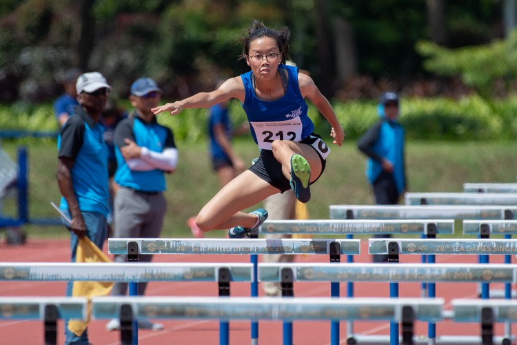 Joanna Seet of Ngee Ann Polytechnic soars over a hurdle in the 100-metre hurdles women's final. (Photo 6 © Jared Khoo/REDintern)