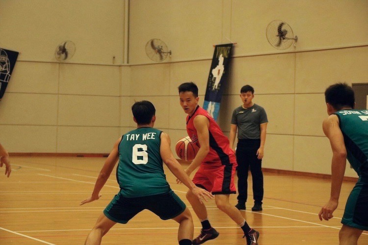 Ronald Yip Lang Jing (#11) caught in action before dribbling past opponent.