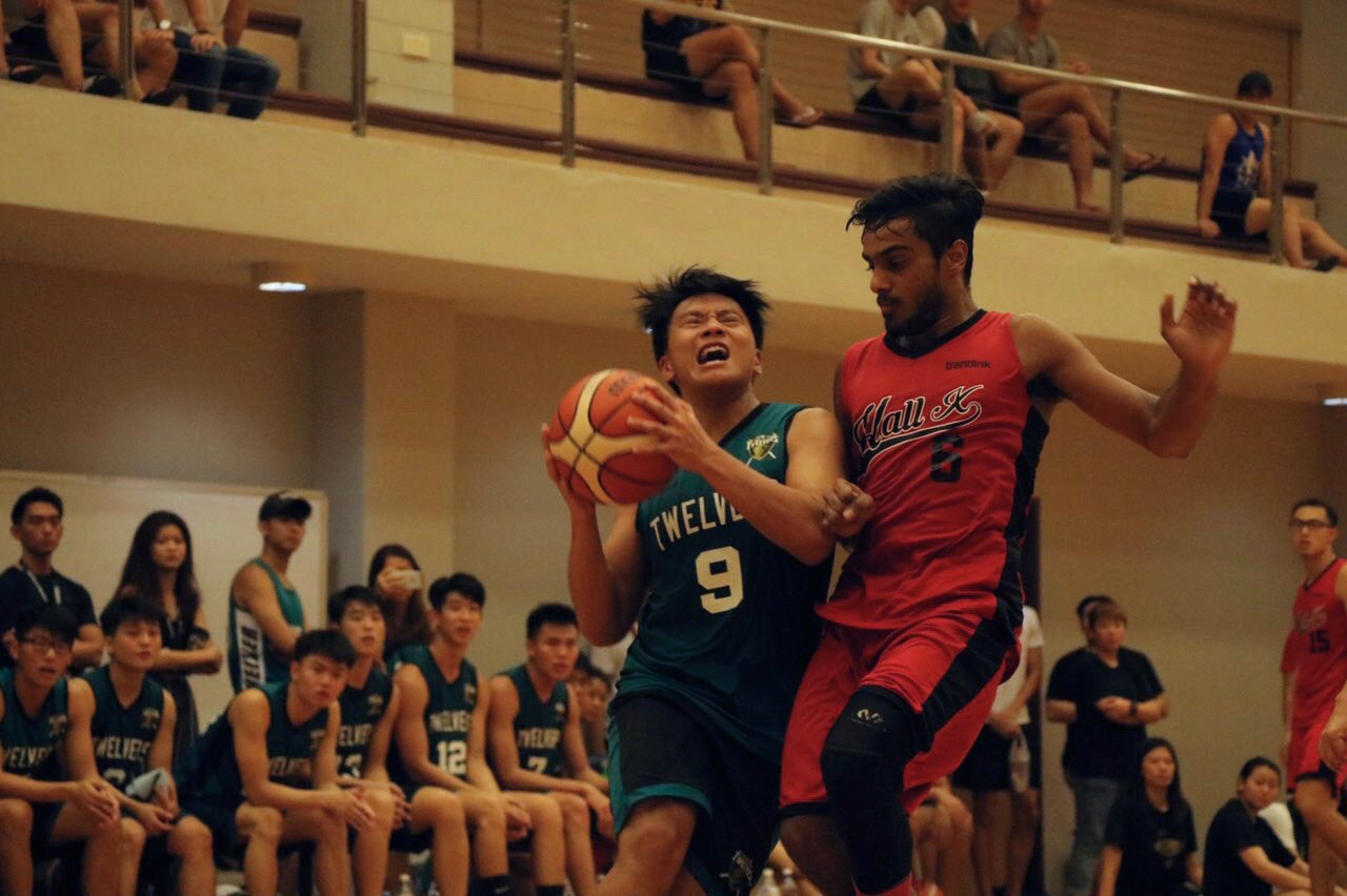 Chua Cheng Wei (#9) of Hall 12 aggressively attempts to get through defender to make the shot.