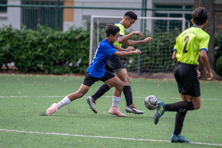Syafi Nur Hilman (#6, in green) of JVSS and Amir Raj (#5, in blue) of CKSS fight for possession. In the foreground: Mhd Zakir (#2) of JVSS.