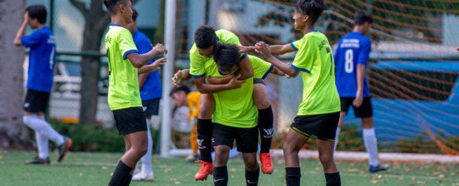 JVSS players celebrating the match-deciding goal. Left to right: Mhd Izrafil (#7), scorer Mhd Arshad (#16) carrying Mhd Izwan (#10), and Raihan Shah (#13).