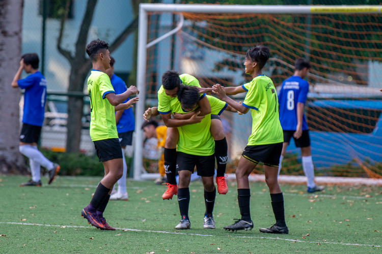 JVSS players celebrating the match-deciding goal. Left to right: Mhd Izrafil (#7), scorer Mhd Arshad (#16) carrying Mhd Izwan (#10), and Raihan Shah (#13).