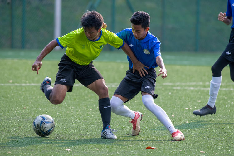 Mhd Arshad (#16, in green) of JVSS and Mhd Aidil (#14, in blue) of CCKSS fight for possession of the ball.