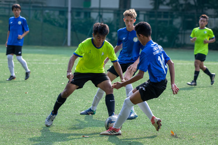 Mhd Arshad (#17) of JVSS attempts to outmaneuver CCKSS players (left to right) Veenstra Dylan (#18) and Mhd Aidil (#14).