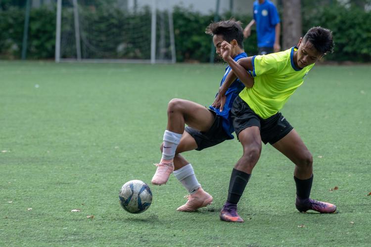 CCKSS captain Adib Hilmy (#17, in blue) fights JVSS player Mhd Izwan (#10, in green) for possession.
