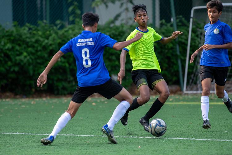 Mhd Izrafil (#7, in green) of JVSS attempts to outmaneuver opponent Febryan Putra Pradana (#8, in blue) of CCKSS.