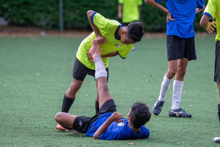 Raihan Shah (#13) of JVSS displays sportsmanship and helps a cramping Adib Hilmy (#17) of CCKSS stretch.