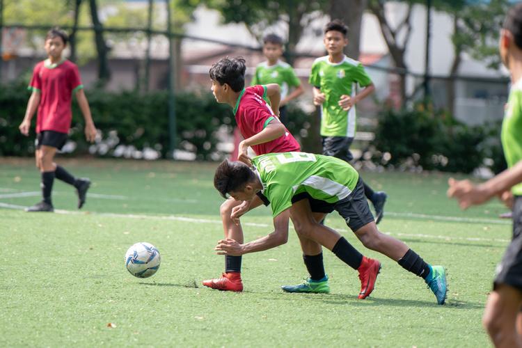 football-bdivOPSS player Izzan (#6) trips over SGS player Tengku Jamaludin (#19). (Photo 9 © Jared Khoo/REDintern)boys-190220-13