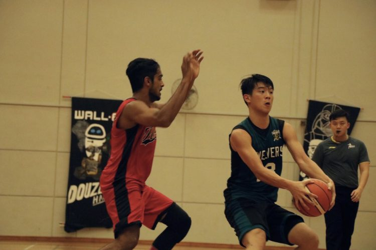 Chong Yih Pin (#13) of Hall 12 catching the ball before dribbling over to shoot.