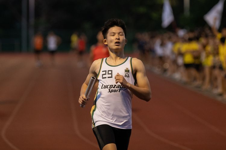 Carl Chua anchoring Temasek Hall in the Men's 4x100m relay. His team got disqualified for a botched baton handover in the second exchange zone. (Photo 5 © REDintern Jared Khoo)