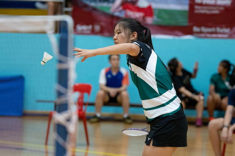 Joanna Wu Chu Jia of Raffles Girls drops the shuttle for a forehand high serve.