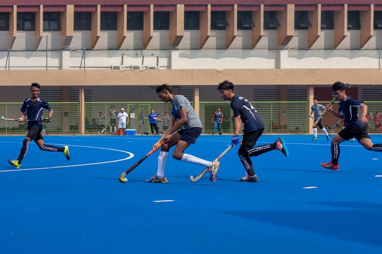 Rishiraj S/O Jaya Kumar (SHS #17) quickly dribbles the ball past the chasing Julian Cheng Hoe Wai (SKS #27). (Photo 9 © REDintern Jordan Lim)