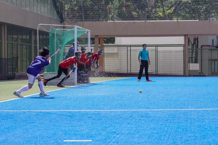 Loh Kuan Meng, Darius (SAS #7) passes the ball from a penalty corner, with Sengkang players tightly defending their goal. (Photo 2 © REDintern Jordan Lim)