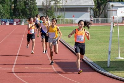 Cheyenne Lim Hwee Suan of SSP crosses the 1500m C Division Girls' final finish line less than a second ahead of runner-up Eryka Anna Kerner Pasupathy of CG (in yellow).
