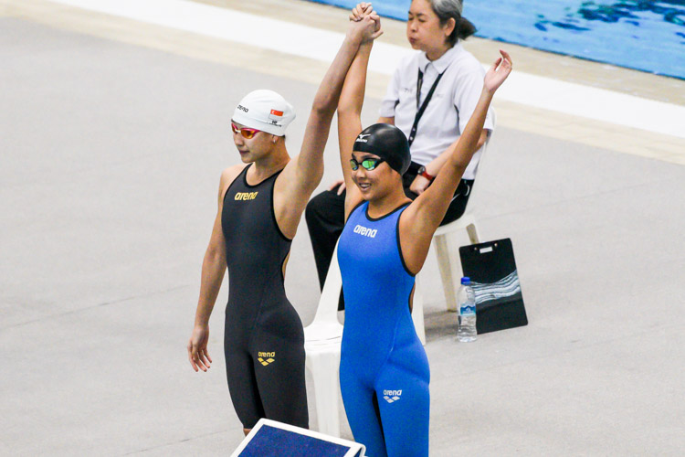 RI teammates Cherlyn Yeoh (left) and Tang Yee Teng acknowledge the crowd before the A Division girls' 100m freestyle final. (Photo 1 © Iman Hashim/Red Sports)