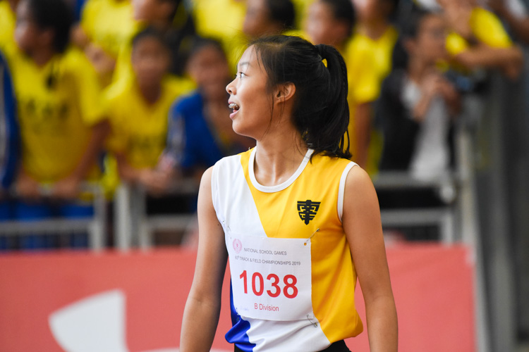 Elizabeth-Ann Tan of Nanyang Girls' High School reacts after seeing the results of the B Division girls' 100m final on the big screen, with her NYGH schoolmates cheering for her in the stands behind. (Photo 1 © Iman Hashim/Red Sports)